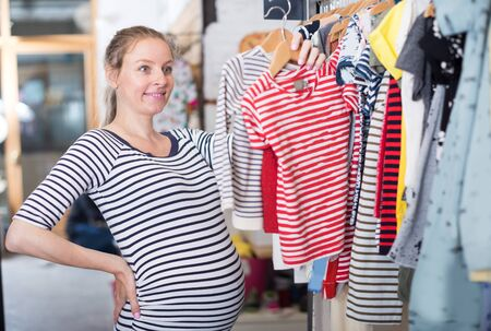 pregnant woman in striped tunic chooses striped shirt in clothing shop Imagens