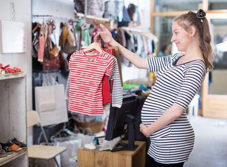 expectant mother In striped tunic shopping Dress in clothing store Imagens