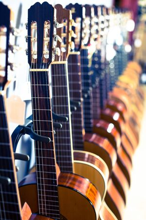 close up hesd of new acoustic guitars in music shop Imagens