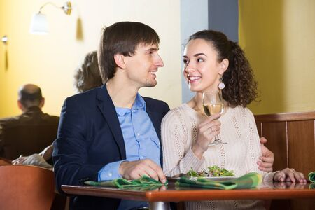 Smiling cute young spouses enjoying tasty dinner in restaurant