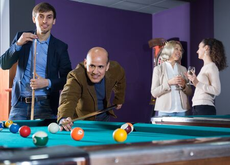 young and the mature man playing billiards Imagens