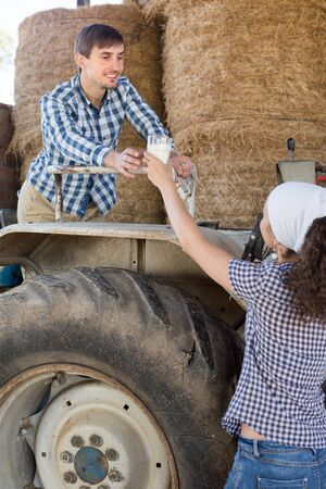 young country woman give to man tractor driver glass of milk on farm Imagens