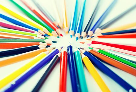 colored pencils lying circle on a white background