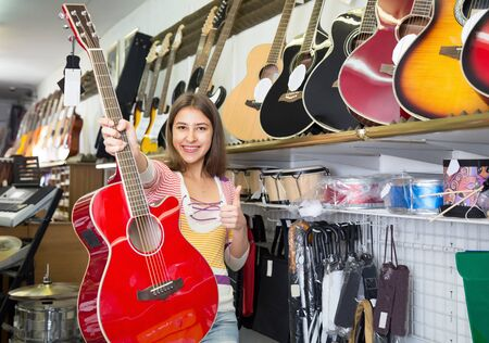 25s girl choising guitar in musical store and smiling