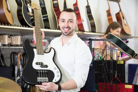 Young male guitarist buying new guitar in store and smiling