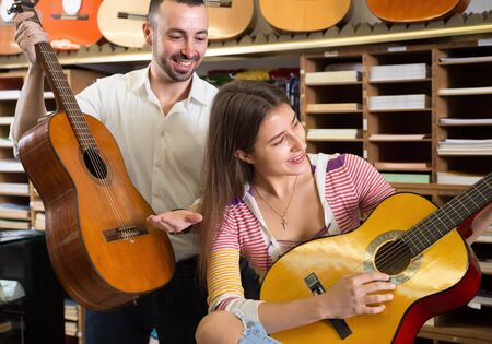 Guitarist girl playing acoustic guitar in music store