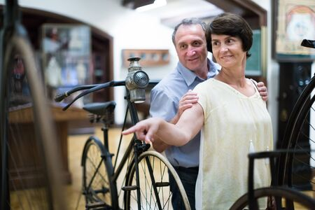 mature couple turists examines the exhibit in historical museum Imagens