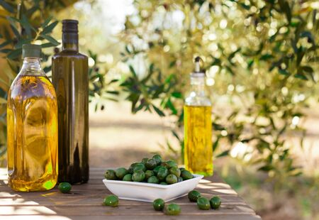 still life with green olives and oil on table in olive grove