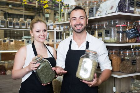 portrait of pair of charming sellers with aprons at store of herbs and ecological food