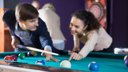 positive smiling young couple hit one ball in billiards, and look at each other. focus on the ball
