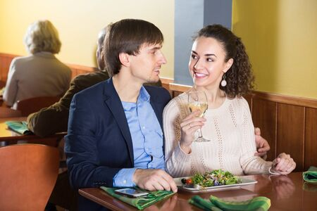 Young man with nice girlfriend talking in restaurant table. fokus on man