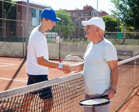 senior and young man shake hands before tennis match