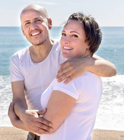 elderly man with a woman in white shirts cuddling on sand on beach and smiling. focus on female