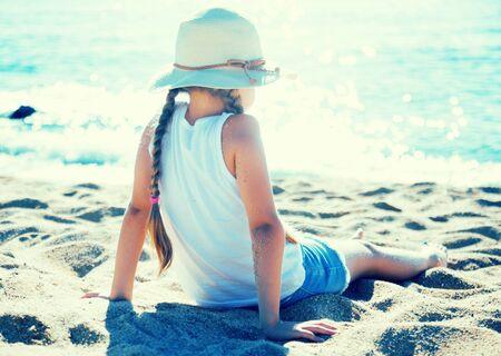 blond child in ha enjoying on sandy beach of sea coast