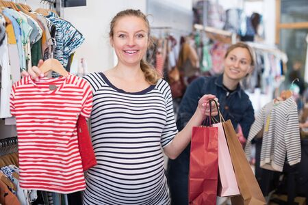 expectant mother In striped tunic shopping Dress in clothing store 免版税图像