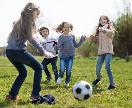 active children run to soccer ball lying on grass