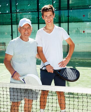 Glad cheerful smiling senior man and young man posing on padel court
