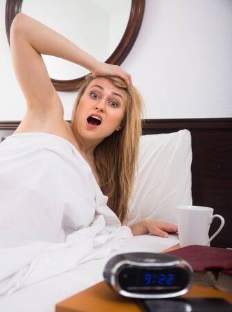 Woman in panic looks at clock