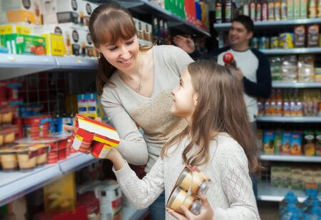 Happy female with daughter buying sweet yoghurts in dairy section