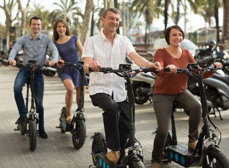group of friends of tourists of different generations enjoy a ride on electric scooters