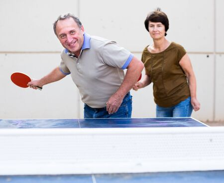 mature couple playing tennis table outdoors