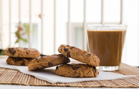 breakfast of cookies with chocolate and hazelnuts and coffee with milk lie on the table