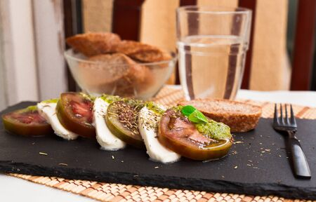 appetizing caprese salad with mozzarella, black tomatoes and pesto on black stone plate Stok Fotoğraf