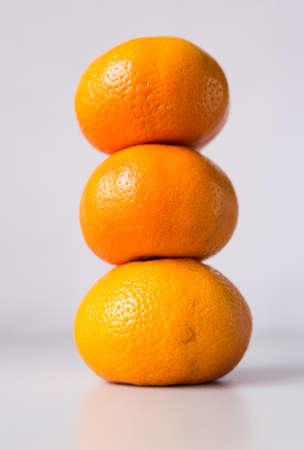 tower of three fresh mandarines on white background Stock Photo