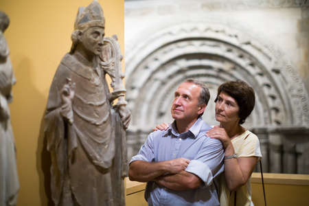 middle aged men and women collector evaluates the exhibition in historical museum