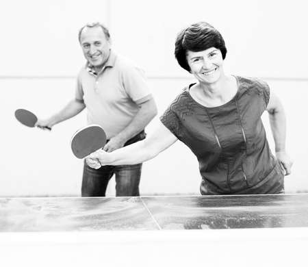 Happy mature man and woman playing table tennis