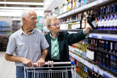mature european couple chooses bottle of wine in alcohol section of supermarket