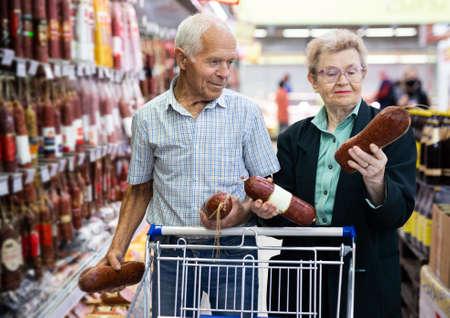 mature European couple chooses out salami in meat section of supermarket Reklamní fotografie