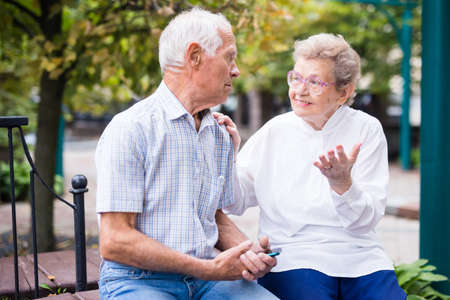mature couple of man with woman sitting on bench in spring