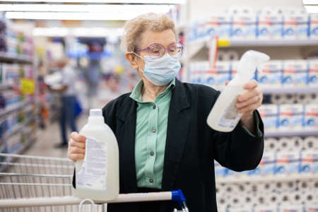 elderly european woman wearing mask and gloves with covid protection chooses disinfectants and detergent in household chemicals department in supermarket
