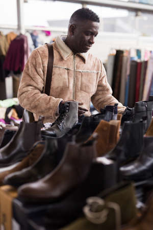 ordinary Afro-American guy considers new shoes on flea market