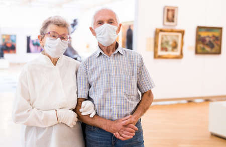 elderly European couple in mask protecting against covid examines paintings on display in hall of art museum
