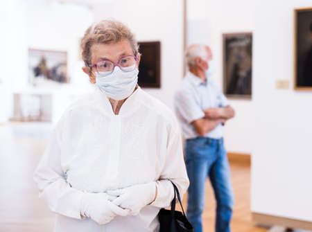 mature woman in mask protecting against covid examines paintings on display in hall of art museum