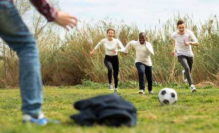 group of multi nationalities teenagers play football through green lawn in summer in park