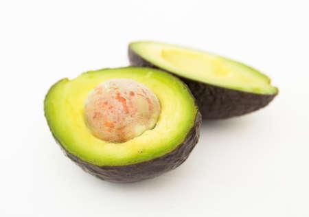 ripe halved avocado with bone on white background Фото со стока
