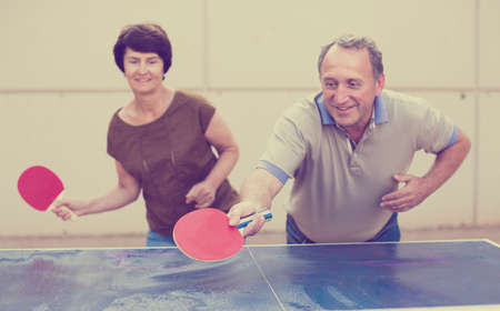 Happy mature spousesn playing table tennis