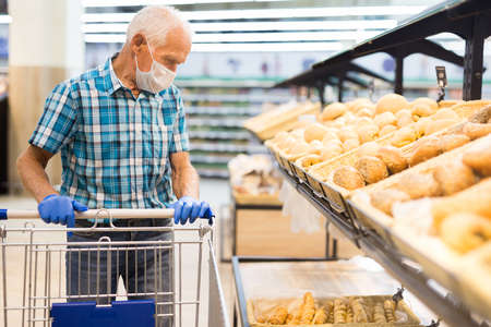 mature european man wearing mask and gloves with covid protection chooses buns and bread in supermarket bakery
