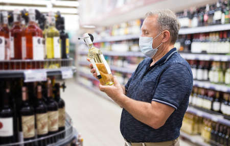 Confident gray-haired elderly man in protective mask choosing white wine in modern wineshop