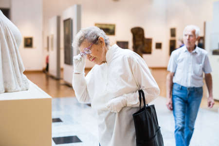 elderly European woman examinessculpture in an exhibition in hall of an art museum