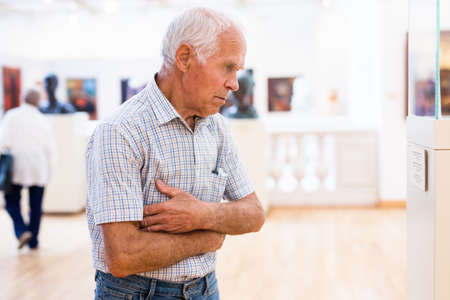 elderly European man examines paintings in an exhibition in hall of an art museum