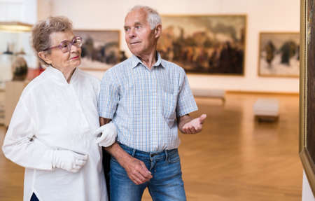elderly European couple examines paintings in an exhibition in hall of art museum