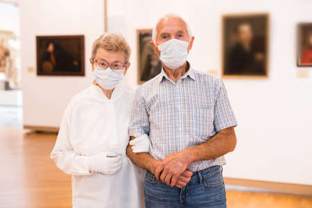elderly European couple in mask protecting against covid examines paintings on display in hall of art museum 免版税图像