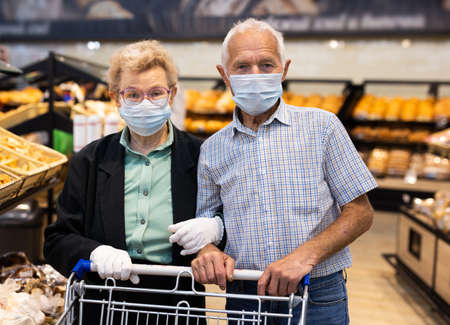 older european couple wearing mask and gloves with covid protection chooses buns and bread in supermarket bakery