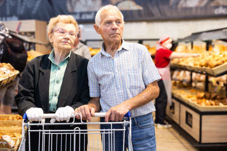 older european couple shopping buns and bread in bakery section of supermarket
