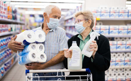 mature european couple wearing mask and gloves with covid protection picks paper towels in department of supermarket Фото со стока