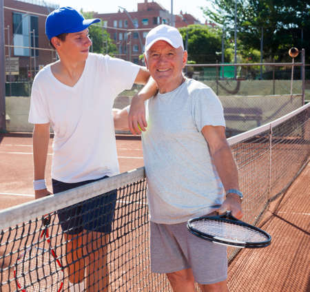 senior man and young man posing on tennis court